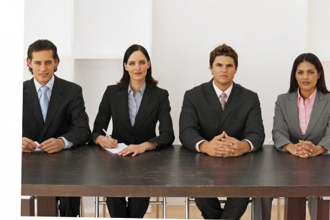 Front view portrait of four business executives sitting in a line --- Image by © Royalty-Free/Corbis